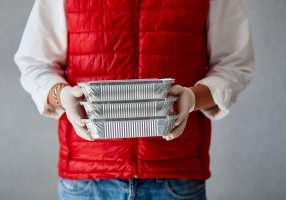 delivery person holding ready made meal boxes in hand